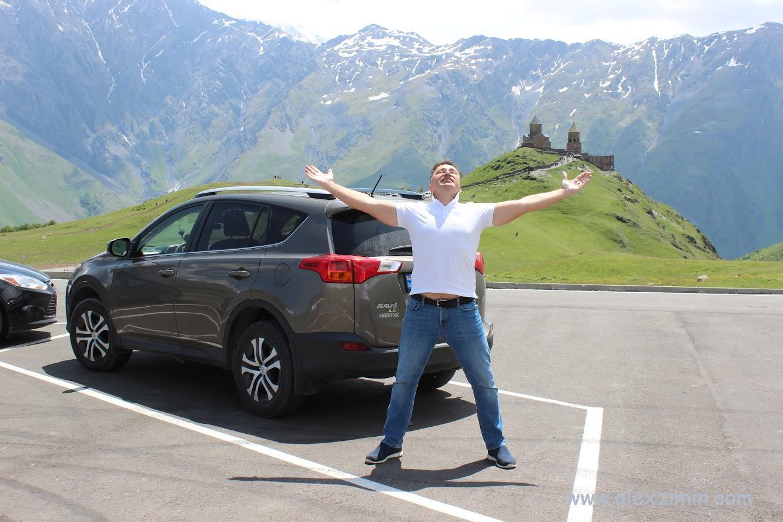 Алексей Зимин на фоне арендованной машины в Грузии