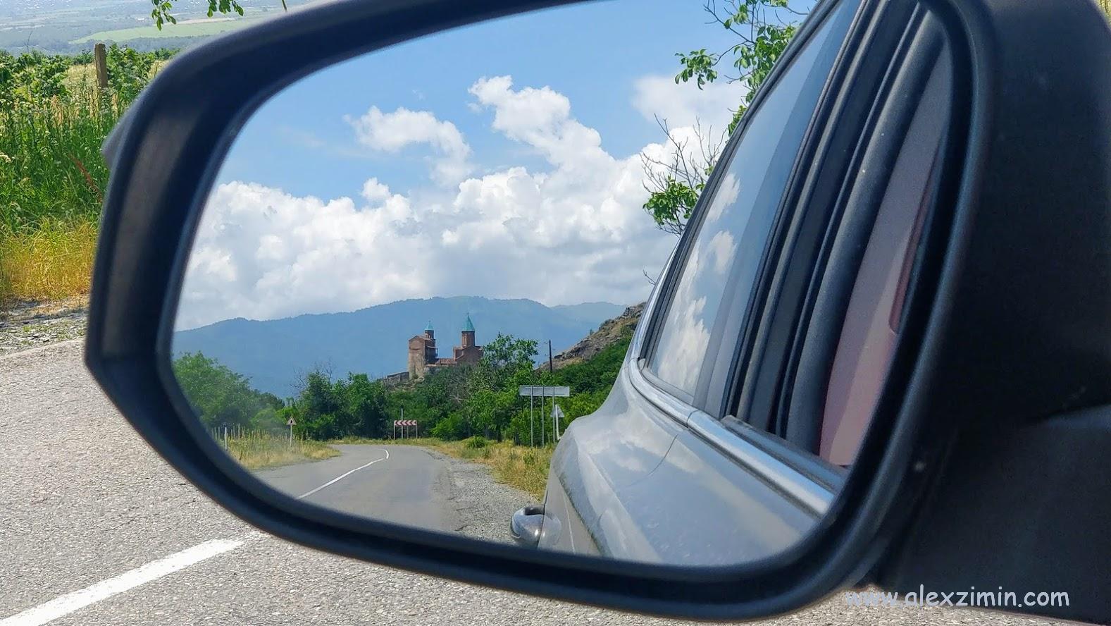 В боковое зеркало машины прекрасно видео грузинскую церквушку